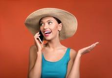 Γυναίκα στο καπέλο που απολαμβάνει την επικοινωνία κινητών τηλεφώνων στοκ εικόνα