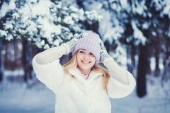 Γυναίκα στο καπέλο που γελά θέτοντας στο υπόβαθρο χιονιού στοκ εικόνες με δικαίωμα ελεύθερης χρήσης