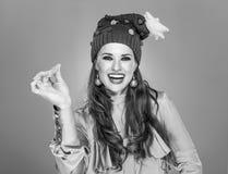Γυναίκα στο καπέλο Χριστουγέννων που απομονώνεται στην γκρίζα θραύση με τα δάχτυλα Στοκ Εικόνες