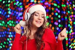 Γυναίκα στο καπέλο santa με τα ακουστικά Στοκ Εικόνα