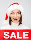 Γυναίκα στο καπέλο αρωγών santa με το κόκκινο σημάδι πώλησης Στοκ εικόνα με δικαίωμα ελεύθερης χρήσης