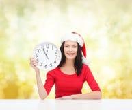 Γυναίκα στο καπέλο αρωγών santa με το ρολόι που παρουσιάζει 12 Στοκ Εικόνες