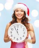 Γυναίκα στο καπέλο αρωγών santa με το ρολόι που παρουσιάζει 12 Στοκ Φωτογραφίες
