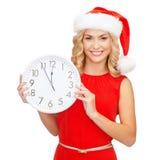 Γυναίκα στο καπέλο αρωγών santa με το ρολόι που παρουσιάζει 12 Στοκ εικόνες με δικαίωμα ελεύθερης χρήσης
