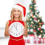 Γυναίκα στο καπέλο αρωγών santa με το ρολόι που παρουσιάζει 12 Στοκ φωτογραφία με δικαίωμα ελεύθερης χρήσης