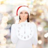 Γυναίκα στο καπέλο αρωγών santa με το ρολόι που παρουσιάζει 12 Στοκ Εικόνα