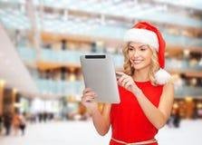 Γυναίκα στο καπέλο αρωγών santa με το PC ταμπλετών Στοκ φωτογραφία με δικαίωμα ελεύθερης χρήσης