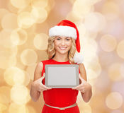 Γυναίκα στο καπέλο αρωγών santa με το PC ταμπλετών Στοκ εικόνα με δικαίωμα ελεύθερης χρήσης