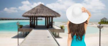 Γυναίκα στο καπέλο μαγιό και ήλιων από πίσω στην παραλία Στοκ φωτογραφία με δικαίωμα ελεύθερης χρήσης