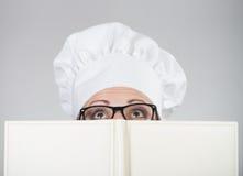 Γυναίκα στο καπέλο του αρχιμάγειρα που κοιτάζει πέρα από το cookbook στοκ φωτογραφία με δικαίωμα ελεύθερης χρήσης