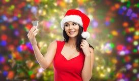 Γυναίκα στο καπέλο santa που παίρνει selfie από το smartphone Στοκ Φωτογραφίες