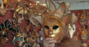 Γυναίκα στο κατάστημα που προσπαθεί στη χρυσή ενετική μάσκα φιλμ μικρού μήκους