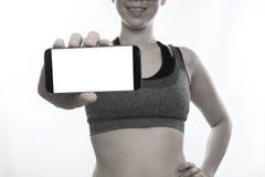 Γυναίκα στο κενό smartphone οθόνης λαβής αθλητικών στηθοδέσμων, ταμπλέτα, κύτταρο Στοκ εικόνα με δικαίωμα ελεύθερης χρήσης