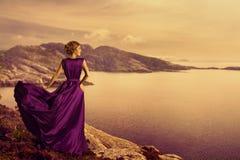 Γυναίκα στο κομψό φόρεμα στην ακτή βουνών, πρότυπη εσθήτα μόδας Στοκ Φωτογραφία
