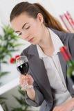 Γυναίκα στο κοστούμι που εξετάζει το κόκκινο κρασί γυαλιού Στοκ εικόνες με δικαίωμα ελεύθερης χρήσης