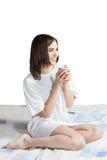 Γυναίκα στο κρεβάτι με τον καφέ Στοκ Φωτογραφίες