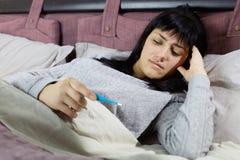 Γυναίκα στο κρεβάτι που ελέγχει τη θερμοκρασία που φαίνεται θερμόμετρο στοκ φωτογραφίες
