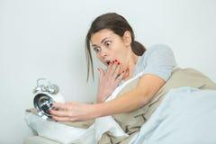 Γυναίκα στο κρεβάτι που εξετάζει στον κλονισμό το ξυπνητήρι στοκ φωτογραφίες με δικαίωμα ελεύθερης χρήσης
