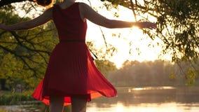 Γυναίκα στο κόκκινο διαφανές φόρεμα που χορεύει και που περιστρέφει γύρω ενάντια στη λίμνη στο ηλιοβασίλεμα φιλμ μικρού μήκους