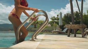 Γυναίκα στο κόκκινο μπικίνι που περπατά έξω της πισίνας μπροστά από τον ωκεανό απόθεμα βίντεο