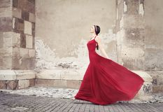 Γυναίκα στο κόκκινο περπάτημα φορεμάτων Στοκ φωτογραφία με δικαίωμα ελεύθερης χρήσης