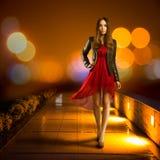 Γυναίκα στο κόκκινο περπάτημα φορεμάτων christmas city fairy latvia night provincial shortly similar tale to Στοκ Φωτογραφία