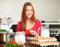 Γυναίκα στο κόκκινο που κατασκευάζει τη ζύμη στην εσωτερική κουζίνα Στοκ εικόνες με δικαίωμα ελεύθερης χρήσης