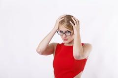 Γυναίκα στο κόκκινο φόρεμα με τα γυαλιά στην πίεση Στοκ φωτογραφία με δικαίωμα ελεύθερης χρήσης