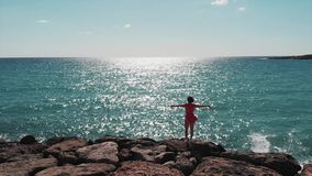 Γυναίκα στο κόκκινο φόρεμα με τα χέρια χώρια στον αέρα που στέκεται στη δύσκολη παραλία απότομων βράχων με τον κηφήνα που πετά γύ απόθεμα βίντεο