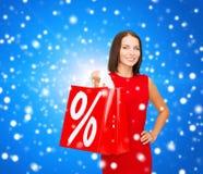Γυναίκα στο κόκκινο φόρεμα με τις τσάντες αγορών Στοκ Εικόνες