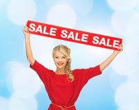 Γυναίκα στο κόκκινο φόρεμα με το σημάδι πώλησης Στοκ φωτογραφία με δικαίωμα ελεύθερης χρήσης