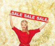 Γυναίκα στο κόκκινο φόρεμα με το σημάδι πώλησης Στοκ Εικόνες