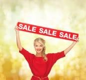 Γυναίκα στο κόκκινο φόρεμα με το σημάδι πώλησης Στοκ Εικόνα