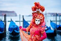 Γυναίκα στο κόκκινο φόρεμα που καλύπτεται για τη Βενετία καρναβάλι μπροστά από τις χαρακτηριστικές βάρκες γονδολών Στοκ Εικόνες