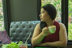 Γυναίκα στο κόκκινο φόρεμα που κρατά το καυτό φλυτζάνι καφέ Στοκ Εικόνες