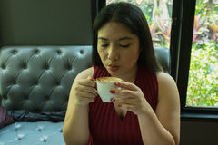 Γυναίκα στο κόκκινο φόρεμα που κρατά το καυτό φλυτζάνι καφέ Στοκ Φωτογραφία