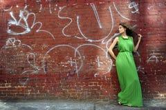 Γυναίκα στο μακρύ πράσινο φόρεμα που στέκεται στον μπροστινό τοίχο Στοκ εικόνες με δικαίωμα ελεύθερης χρήσης