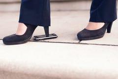 Γυναίκα στο μαύρο βήμα παπουτσιών τακουνιών στο τηλέφωνο Στοκ Φωτογραφίες