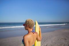 Γυναίκα στο μπικίνι και γυαλιά ηλίου που στέκονται με την ιστιοσανίδα στην παραλία στην ηλιοφάνεια στοκ φωτογραφίες με δικαίωμα ελεύθερης χρήσης