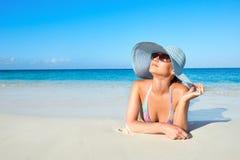 Γυναίκα στο μπικίνι και θερινό καπέλο που απολαμβάνει στην τροπική παραλία στοκ εικόνες