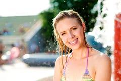 Γυναίκα στο μπικίνι που κάνει ηλιοθεραπεία στο aquapark Θερινά θερμότητα και νερό Στοκ Φωτογραφίες
