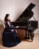 Γυναίκα στο μπλε φόρεμα δαντελλών βαθιά που παίζει το πιάνο και τα λουλούδια διανυσματικός τρύγος ύφους απεικόνισης αναδρομικός στοκ εικόνα με δικαίωμα ελεύθερης χρήσης