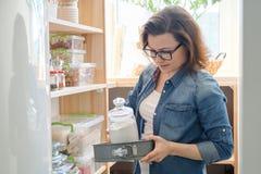 Γυναίκα στο οψοφυλάκιο κουζινών Ξύλινη στάση αποθήκευσης με το σκεύος για την κουζίνα, προϊόντα απαραίτητα να μαγειρεψουν στοκ φωτογραφία
