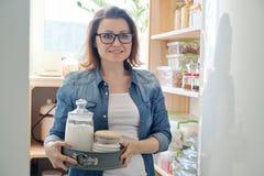 Γυναίκα στο οψοφυλάκιο κουζινών Ξύλινη στάση αποθήκευσης με το σκεύος για την κουζίνα, προϊόντα απαραίτητα να μαγειρεψουν στοκ φωτογραφία με δικαίωμα ελεύθερης χρήσης
