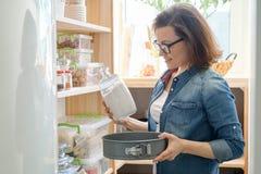 Γυναίκα στο οψοφυλάκιο κουζινών Ξύλινη στάση αποθήκευσης με το σκεύος για την κουζίνα, προϊόντα απαραίτητα να μαγειρεψουν στοκ εικόνες