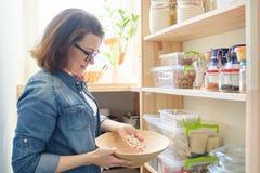 Γυναίκα στο οψοφυλάκιο με το κύπελλο των άσπρων φασολιών Γραφείο αποθήκευσης στην κουζίνα στοκ φωτογραφία
