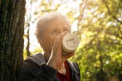 Γυναίκα στο πάρκο που κλίνει ενάντια στο δέντρο και που πίνει coffe στοκ φωτογραφίες