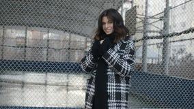 Γυναίκα στο παλτό κοντά στον καθαρό φράκτη απόθεμα βίντεο