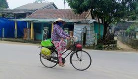 Γυναίκα στο παραδοσιακό ασιατικό κωνικό καπέλο στο bycicle Στοκ Φωτογραφίες