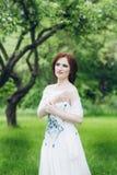Γυναίκα στο πολύ άσπρο φόρεμα στο θερινό κήπο Στοκ Φωτογραφία